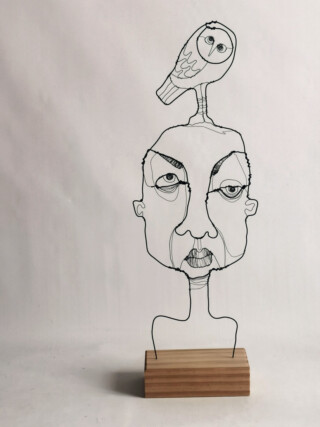 Interior Wire sculpture of a face with a Little Owl on his head. Mounted on wooden block