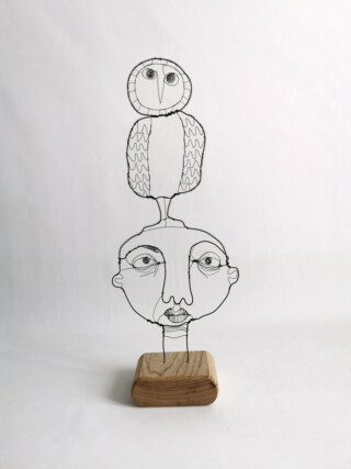 Small wire sculpture of a face with a large owl above mounted on wooden block
