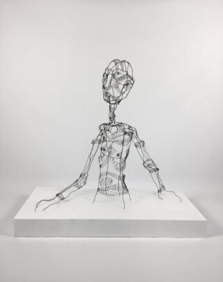 Wire sculpture of man appearing out of a plinth. Stargazer by Fiona Morley
